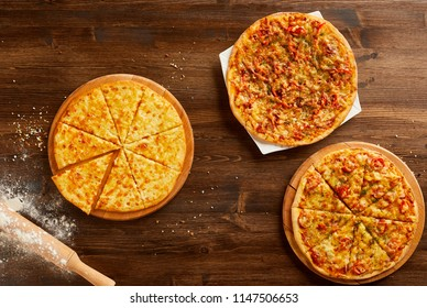 Top view of variety of pizzas on wooden table