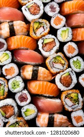 Top view of variety of sushi food. High angle view of nigiri, maki, hosomaki, uramaki and roll with tuna, salmon, avocado and shrimp in a row. Traditional japanese food with raw fish and rice.