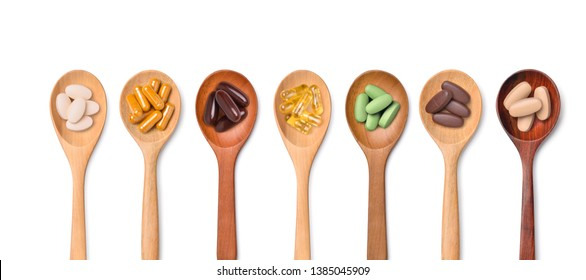Top view Variety of vitamin and mineral pills in wooden spoon isolated on white background, Dietary supplement healthcare product.