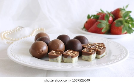 Top view of various chocolate pralines ,strawberrys and pearl necklace on white background.Exclusive chocolate candies. Product concept for chocolatier. Feminine styled stock image.