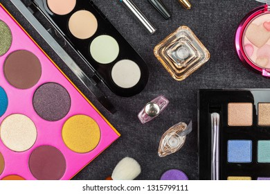 top view of various decorative cosmetics including eye shadows, powder, concealers and perfumes. concept of professional makeup