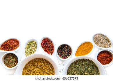 Top view of various dried aromatic spices in ceramic spoons and bowls isolated on white