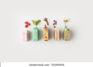 top view of various handcrafted soap with different ingredients in row on white surface