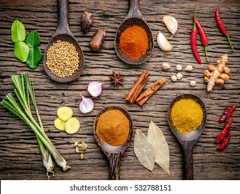 Top view of various herbs and spices in spoon on rustic brown wooden background in concept of healthy lifestyle. Preparation ingredients for spicy menu. Asian culture and foods.