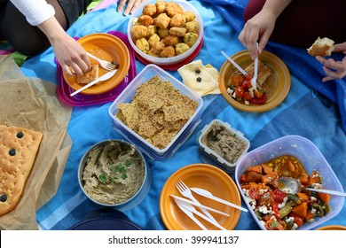 Top view of various picnic food: vegetable and feta salad, baba ghanoush, healthy crackers, rice fritters and olive bread.