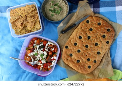 Top view of various picnic food: roasted vegetables and feta salad, baba ghanoush, gluten-free crackers and foccacia.
