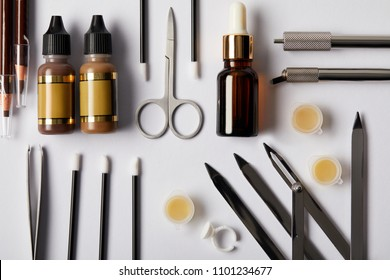 top view of various tools and cosmetics for permanent makeup on white