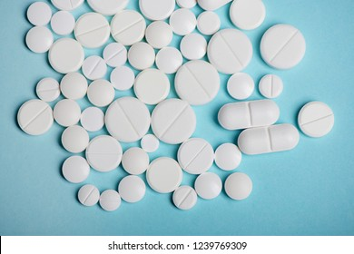 Top view of various white pills on blue background
