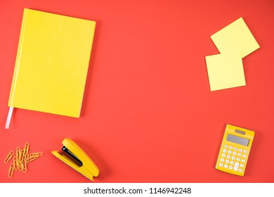 top view of various yellow office appliances on red