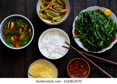 Top view vegan Vietnamese food for lunch, bowl of rice, boiled water spinach, salted cucumber, fried egg, tomato soup, homemade vegetarian meal with vegetables for vegan diet