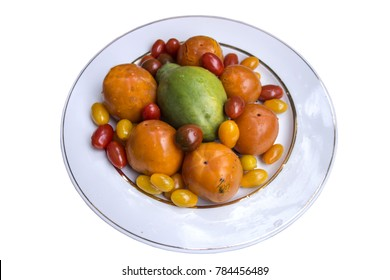 Top view vegetables and fruits: finger tomatoes of different colors, persimmon and papaya isolated on white background for vegans and vegetarians ready for product display or montage.