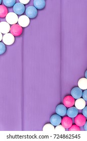 Top view of vertical frame made of colored chocolate coated candy on wooden purple background. Copy space