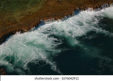 Top view of very low but wide waterfall with deep turquoise colored water filled with air bubbles