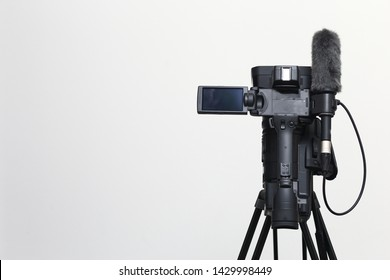 The top view of video camera with the microphone is standing on the tripod isolated on white, in concept of technology, modern, entertainment.