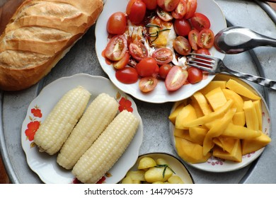 Top view of Vietnamese food tray, nutritious meal for lunch with bread, tomato, potato, eggs, mango, boiled corn, suitable for non meat, diet or vegetarian