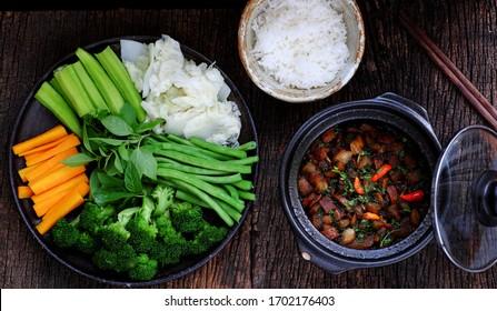 Vue de dessus repas vietnamien pour le déjeuner végétarien, assiette de légumes bouillis et sauce braisée végétalienne en pot, délicieux plat prêt à manger avec du riz, repas quotidien sain sur fond bois foncé