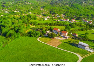 Top view of the village houses with red tiled roof on the green grass