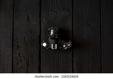 top view of vintage dslr 35mm film camera on dark wooden table