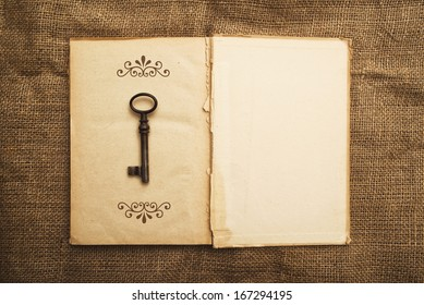 Top View of Vintage open book with old grunge paper textured pages and rusty key