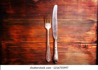 Top view of vintage silver knife and fork on brown wooden textured table. Classic table setting concept. Close up, copy space for text, background, flat lay.