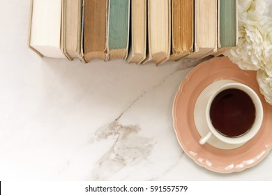 Top view of vintage styled desktop with worn books, coffee and flowers. Open marble space for copy