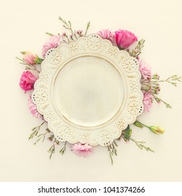Top view of vintage white empty plate over spring flowers. Flat lay