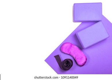 Top view of violet yoga mat, two violet blocks and violet belt, silky eye pillow isolated on white background with copyspace. Yoga practice, relaxation and meditation concept