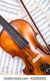 Top view of violin and bow on musical score