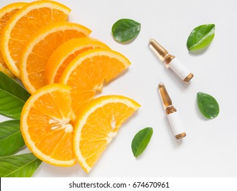 Top view of vitamin C brown ampule for injection with fresh juicy orange fruit slides and green leaves on white table.
