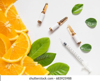 Top view of vitamin C brown ampule for injection and syringe with fresh juicy orange fruit slice and green leaves on white table. Vitamin/mineral supplement concept. Beauty product mock-up.