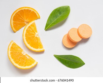 Top view of vitamin c effervescent tablets with fresh juicy orange fruit slice and green leaf on white table. Vitamins from foods or supplements choices. Health and medical concept.