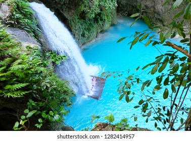 Top view of the waterfall. The original Kawasan waterfall, falling streams of water in a pure turquoise lake, among the greenery of tropical ferns and vines. Cebu, Philippines.