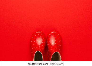 top view of watertights rain season concept. new children's stylish gumboots on red background. overhead photo of red watertights with copy space