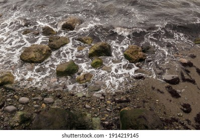 A top view of waves hitting a rocky seasho
