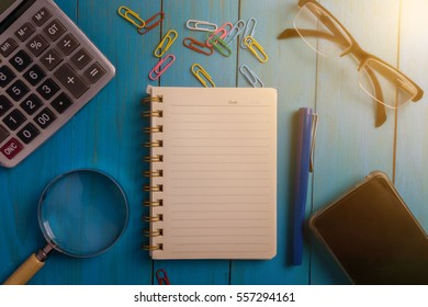 Top view of WEBINAR written on the notebook,magnifier glass,calculator,smart phone,pen and glasses on blue wooden desk.business concept.