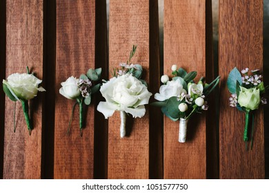 Top view of wedding boutonniere for the groom and bridesmaids on wooden background, free space. Wedding details outdoor with copy space. Wedding morning preparation