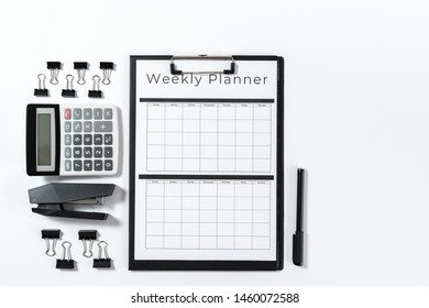 Top view of weekly planner in clipboard, calculator, stapler and stationery isolated on white background with copy space