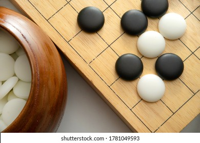 top view of weiqi-baduk-igo board game (This is an adversarial game with the objective of surrounding a larger total area of the board with one's stones than the opponent)