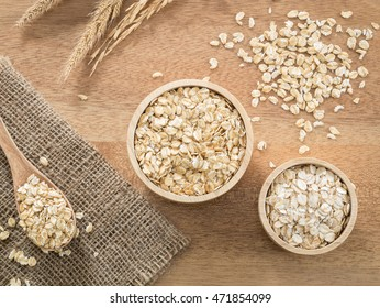 Top view -  Wheat flakes and barley flake in wooden bowl on wooden background - Raw food ingredients
