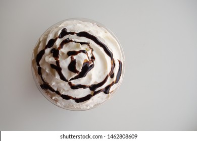 Top view of whipping cream with chocolate syrup on white background. Sweet topping of drink. Dessert and drink background with copy space.