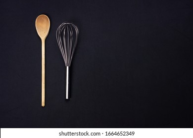 Top view of a whisk and a wooden spoon. Dark and dramatic light. Black background. Right copy space. Studio photo