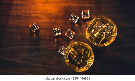 Top view whiskey in glass with beautiful amber ice,placed on wooden table with rough surface against dark background and bokeh, with an alcoholic concept. drinks for celebrations and parties at night