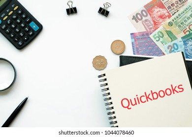 Top view white backgorund desktop with Hong Kong Bank Note Money Notebook write text Quickbook for Accounting concept.