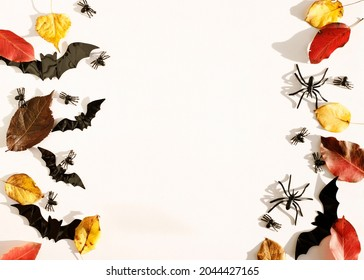 Top view white background with bats, spiders and autumn leaves with copy space for text. Mock up of Halloween holiday concept.