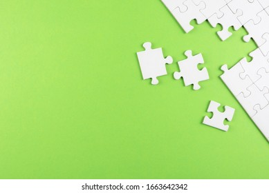 top view of white blank unfinished jigsaw puzzle on green background, completing a task or solving a problem concept