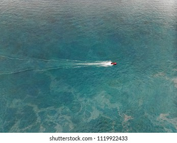 Top view of a white boat sailing in the blue sea.