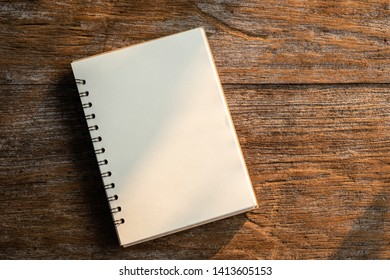 Top view of white book on old wooden plank background with morning nature sunlight