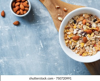 Top view of the white bowl with muesli with almond nuts and dried berries in  on the blue textured table. Copy space.