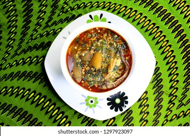 Top view of a white bowl of okra soup with cow skin meat (Nigerian kpomo) and dried fish served on a colorful green table cloth