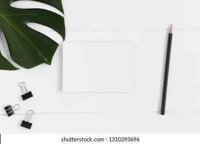 Top view of a white card mockup with workspace accessories and a monstera leaf on a white table.